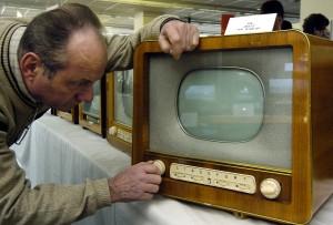 Der Ausstellungsbetreuer Joachim Hartung hantiert in einer Ausstellung in Staßfurt an einem Fernsehgerät vom Typ «Iris», dem ersten Fernseher, der 1957 in Staßfurt gefertigt wurde, am 17.02.2004. Foto: Peter Förster (zu dpa «Rennen der Testbilder - Vor 60 Jahren startete das deutsche Fernsehen» vom 17.12.2012)