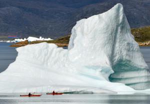 Zwei Kajakfahrer passieren am 03.09.2010 einen Eisberg im Fjord von Narsaq (Grönland). Eisberge entstehen, wenn Gletscher schmelzen. Forschungen zeigen, dass auch die als stabil geltenden Gletscher in Grönland Eis verlieren. (Foto: Wolfgang Heumer/dpa)