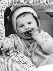 Ein kleines Kind in einem Kinderwagen futtert am 21.05.1964 Schokolade. Mund und Hände sind bereits völlig von der schmelzenden Leckerei verschmiert. Die Babyboomer-Jahrgänge der 60er Jahre haben sich nach Einschätzung des Historikers Nolte nicht zu einer richtigen Generation vergleichbar mit den 68ern entwickelt. Die 64er waren der geburtenstärkste Jahrgang in der deutschen Geschichte. (Foto: dpa)