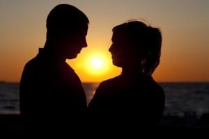 ARCHIV - Ein Paar steht bei Sonnenuntergang am Ostseestrand von Warnemünde, aufgenommen am 23.06.2009. Immer mehr Menschen leben trotz fester Beziehung in getrennten Wohnungen. Foto: Arno Burgi/dpa
