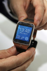 """Ein Mann präsentiert die Smartwatch """"Samsung Gear 2"""" auf dem Mobile World Congress in Barcelona im Februar 2014."""